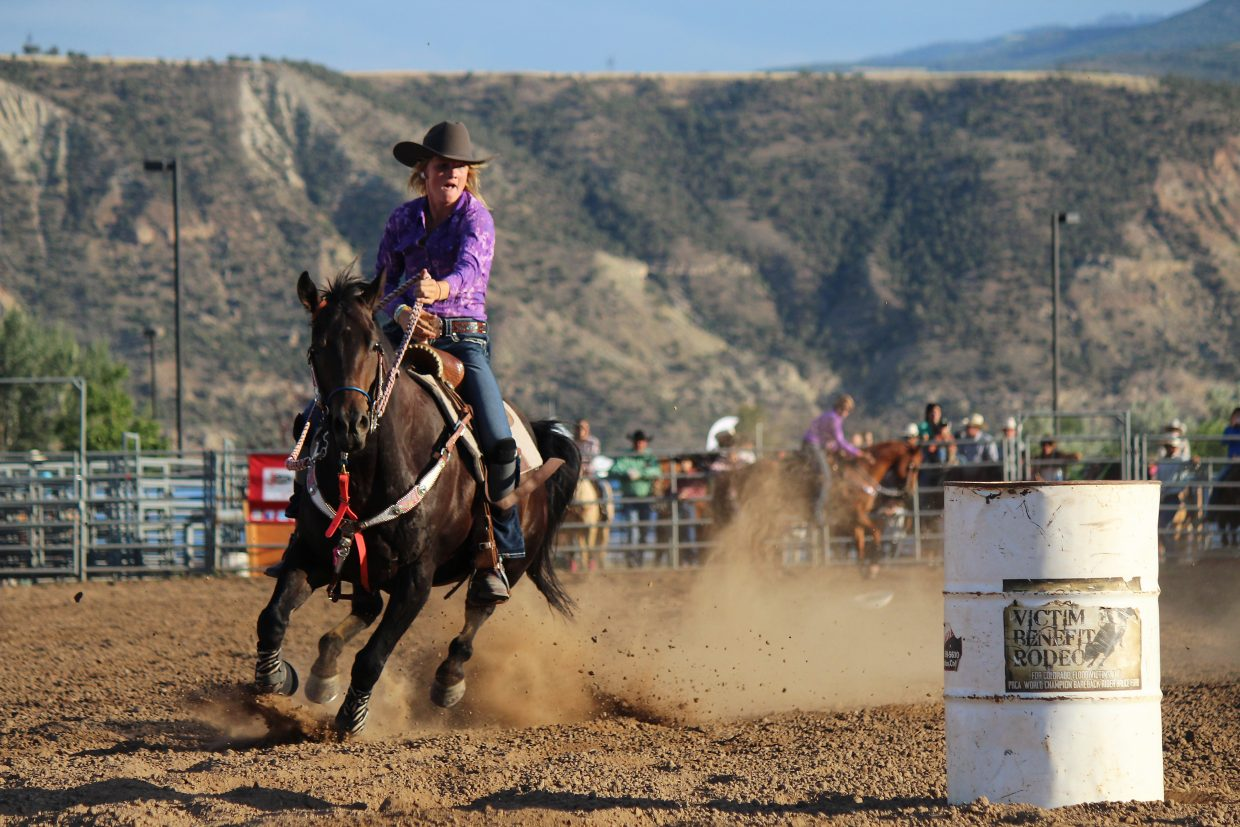 Kathryn Sauerwein rides in the family barrel racing event during family rodeo night at the 2016 Garfield County Fair and Rodeo in Rifle Monday.
