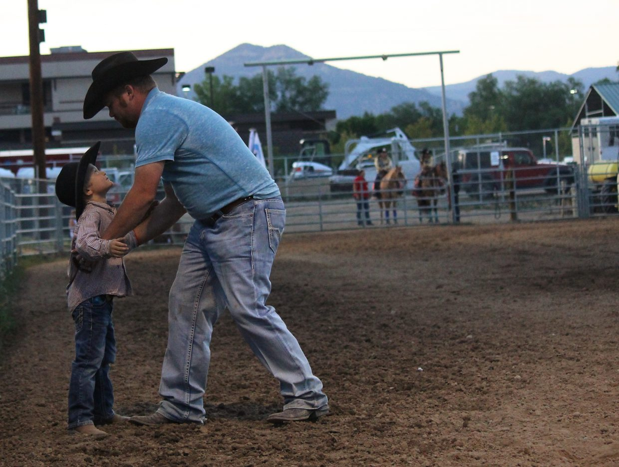 Chance Jenkin goes to lift his son, Caeson, at the 2016 Garfield County Fair and Rodeo in Rifle Monday night.