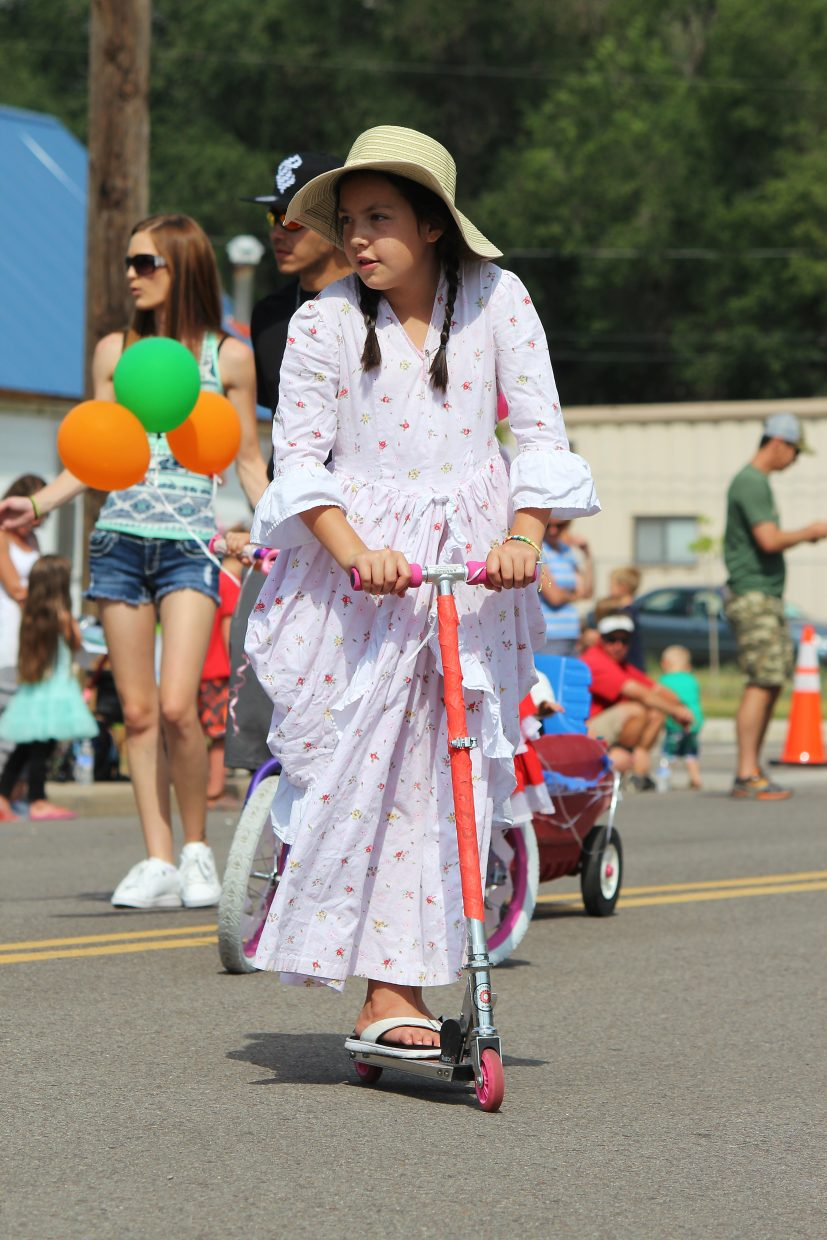 Wearing historical-era clothing, Trinity Trent rides a scooter down Parachute Avenue in the Grand Valley Days parade.