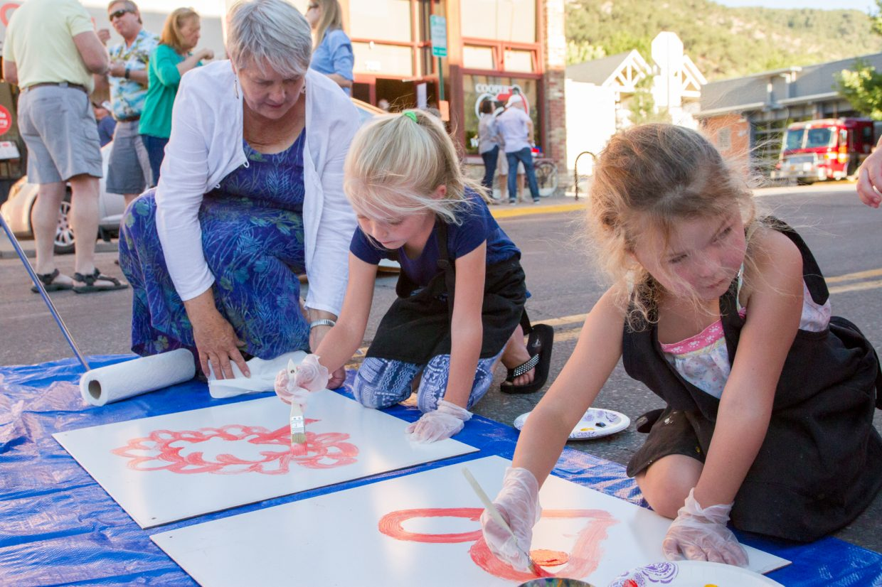 Artist Nancy Martin helping six-year old Rose Durrett with her paining that will be part of a mural to cover up the plywood seperating the Grand Avenue pedestrian and traffic bridges.