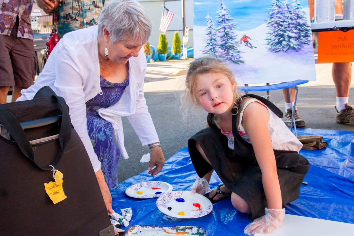 Nancy Martin helping five-year old Ava Mehus start her painting at the art station in front of the Cooper Corner Art Gallery.