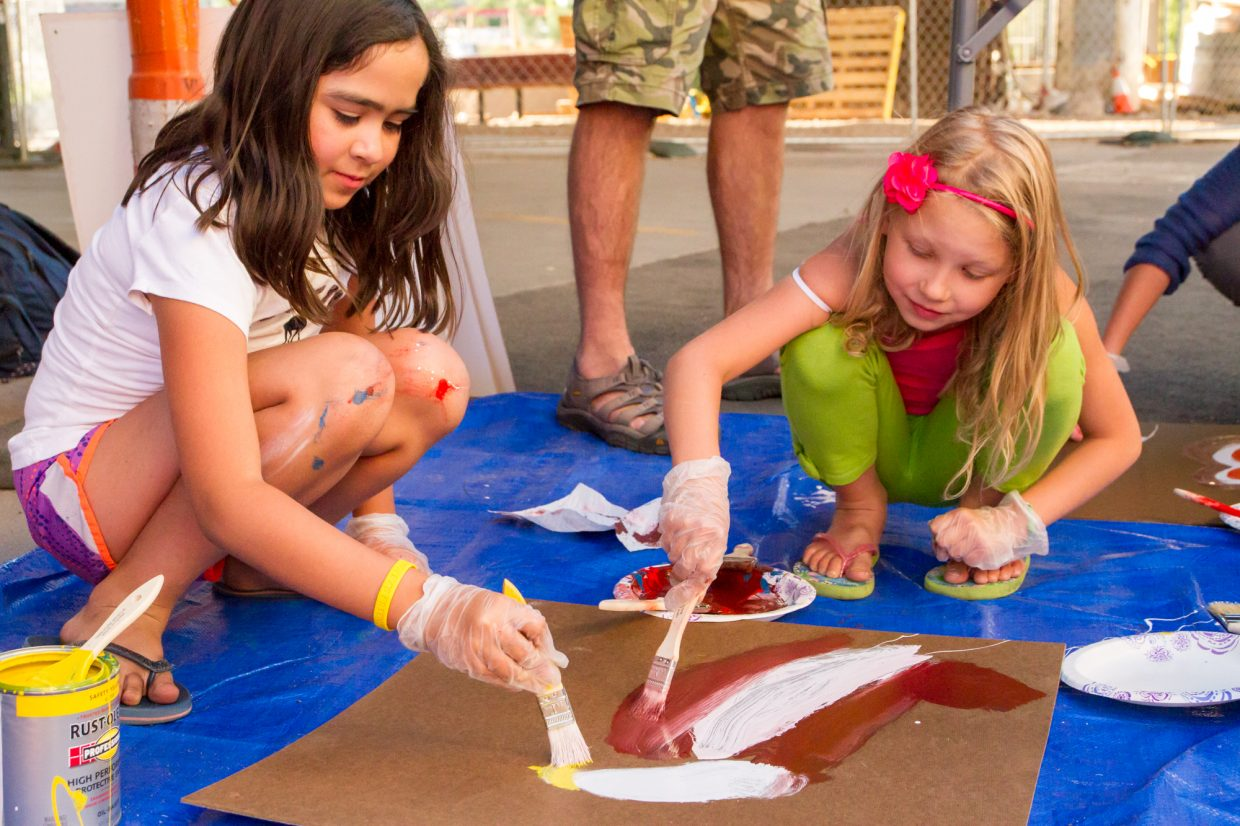 Nine-year old Yathziry Ortega (left) and her friend Isabella Duplesys (7) painting at the art station located under the Grand Avenue Bridge near the Riviera Supper Club.