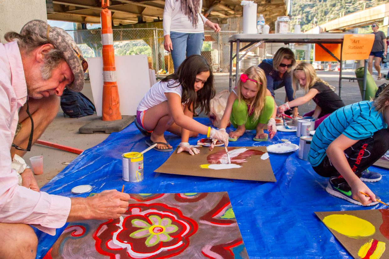 A group of kids and adults painting at the art station under the bridge and near the Riviera Supper Club the second Glen-A-Palooza.