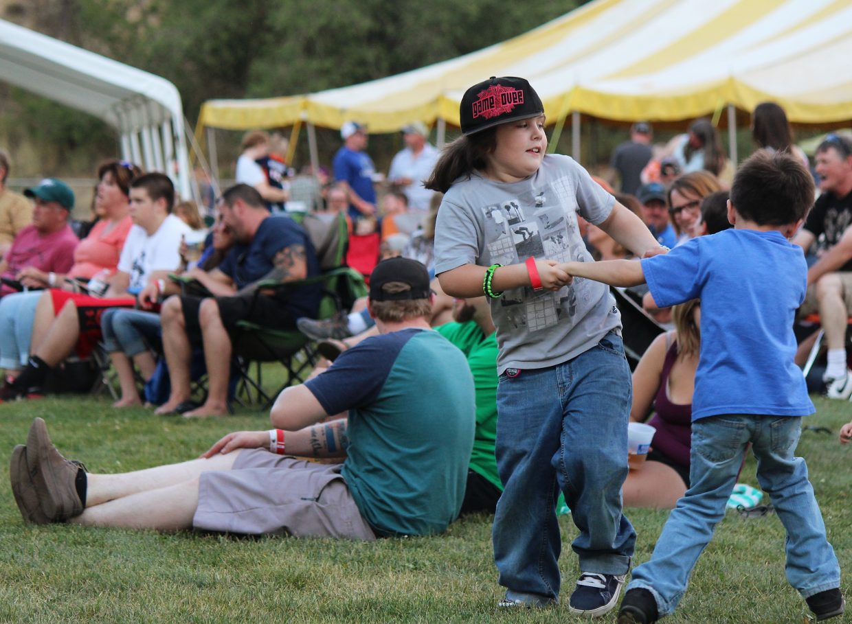 Conner, left, and Aaron Enlow spin each other around while the Corporation Band featuring the Sisters of Rock perform Friday.