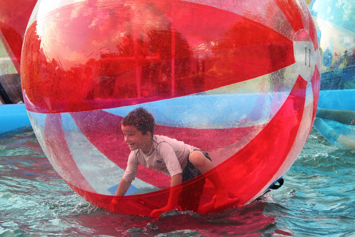 Gage Chelewski prepares to spring forward in a giant ball floating in a pool.