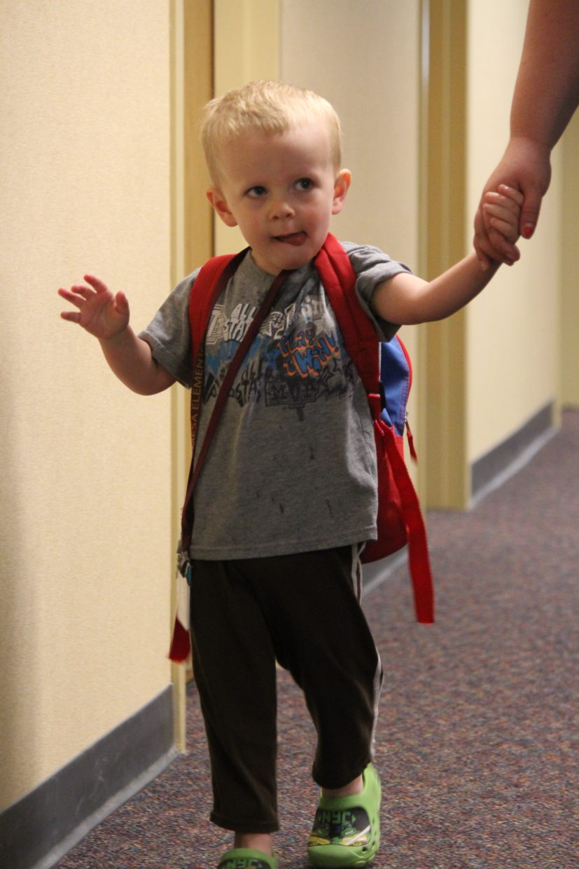 Aspiring student Dillon Clements walks the halls at Graham Mesa Elementary School with his mother Monday after dropping off his twin brother and sister. Both are in the first grade.