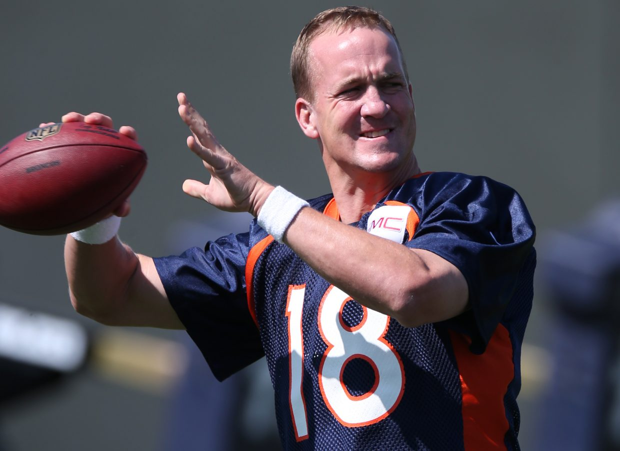 FILE - In this July 25, 2014, file photo, Denver Broncos quarterback Peyton Manning throws football during drills at the morning session of the team's NFL football training camp in Englewood, Colo.Manning was Denver's de facto drill sergeant over the last four seasons, and as they begin the post-Peyton era, the Broncos say they're just as fastidious in his wake as they were in his presence. (AP Photo)