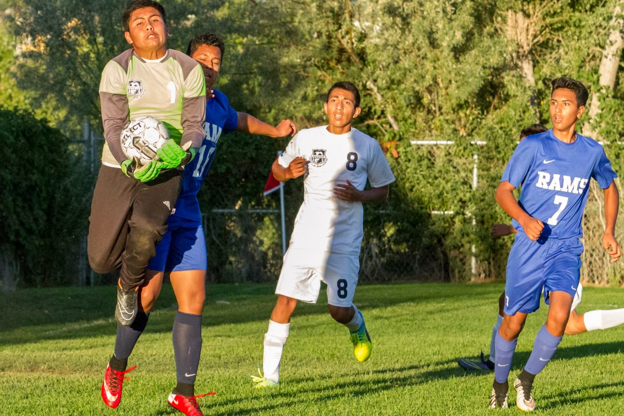 Rifle freshman goalkeeper Isaac Rivas secures a shot during Tuesday's game against Roaring Fork as Rifle junior Oscar Crispin (center),and Roaring Fork attackers Mikel Mayo (left) and Ariahn Barajas (right) look on.