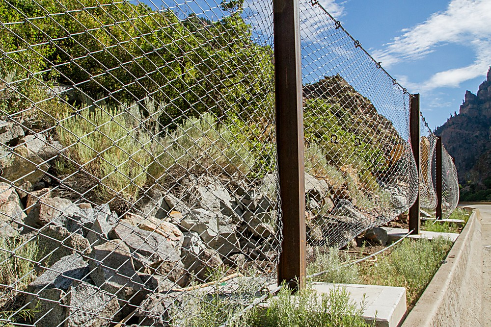 A fence holds back some of the smaller rocks that have tumbled down the north face of Glenwood Canyon west of Hanging Lake.