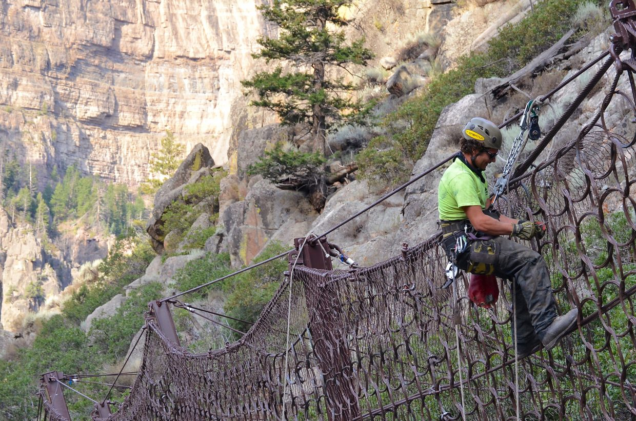 Suspended over a steep hillside above Interstate 70, a crew member puts the finishing touches on one of the rockfall barrier fences in Glenwood Canyon.