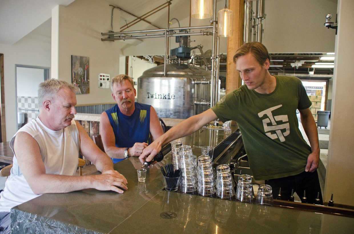 Max Vogelman pours a sample for Rob Hubler and Jim Kelly.