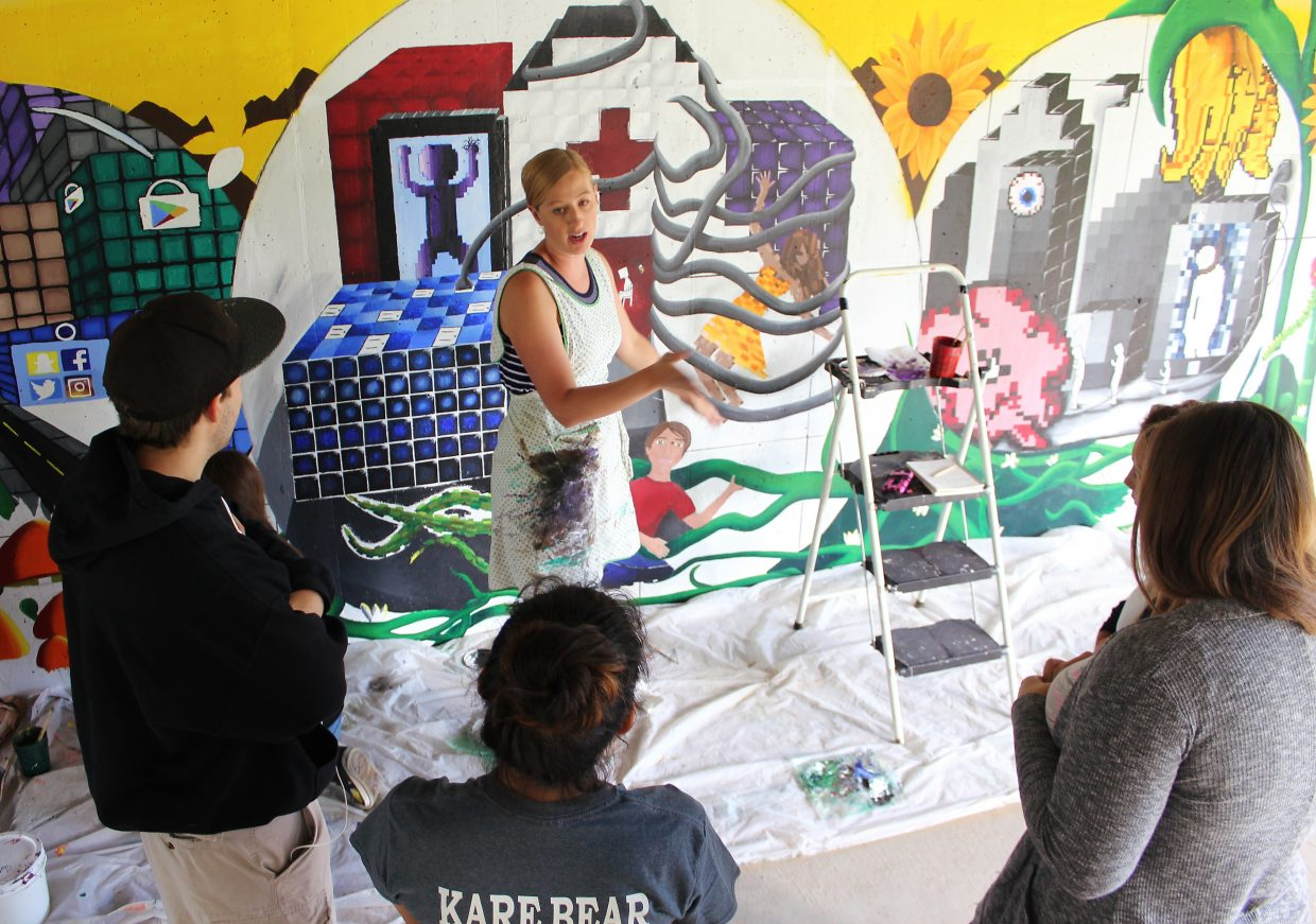 Art instructor Mandy Klauck shares some advice with local artists working on a mural in Rifle.