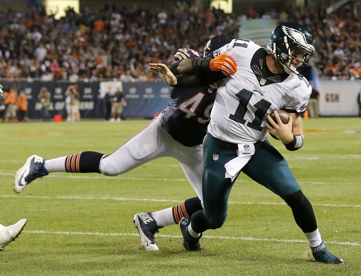 Philadelphia Eagles quarterback Carson Wentz (11) runs against Chicago Bears outside linebacker Sam Acho (49) during the first half of an NFL football game, Monday, Sept. 19, 2016, in Chicago. (AP Photo/Charles Rex Arbogast)