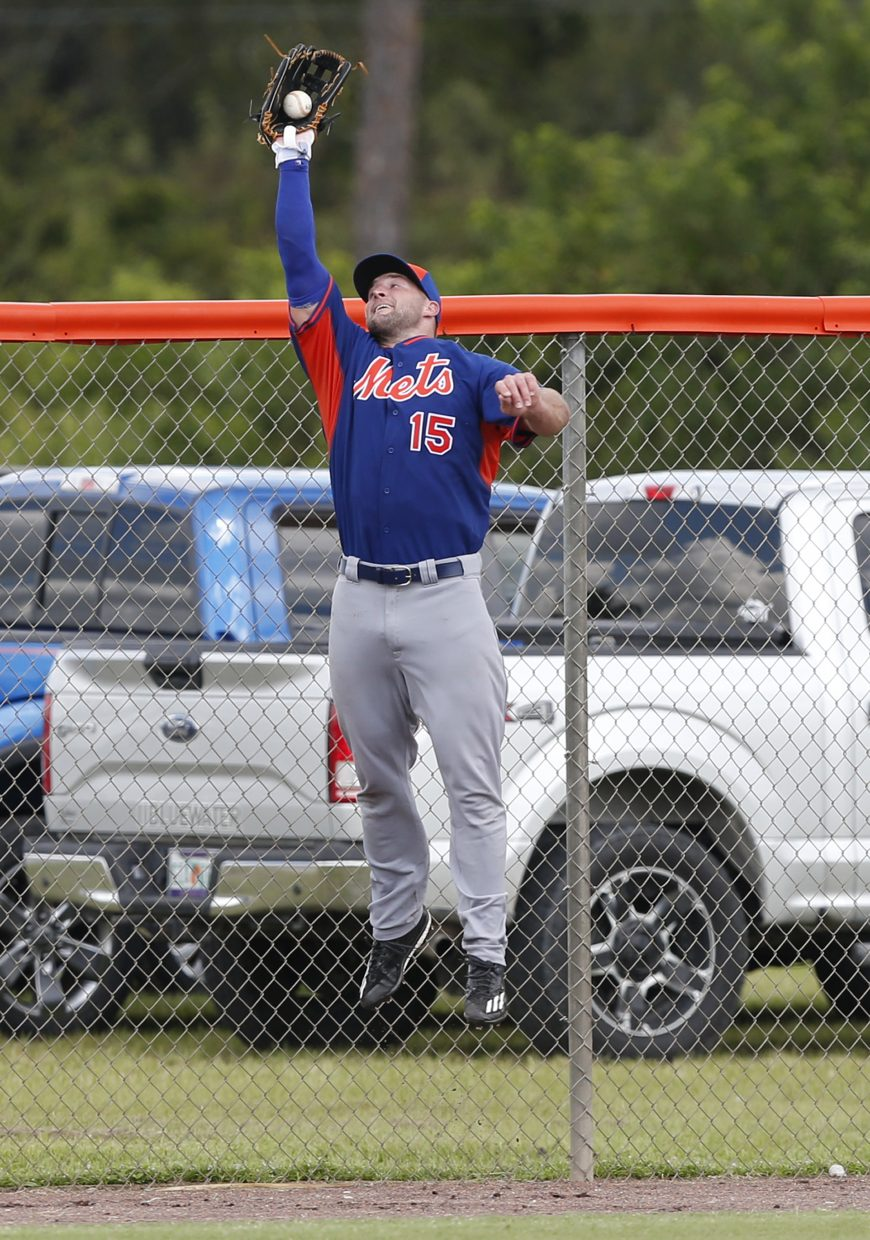 Tim Tebow catches a ball at the fence during a drill at the New York Mets' complex, Monday, Sept. 19, 2016, in Port St. Lucie, Fla. The 2007 Heisman Trophy winner and former NFL quarterback got to the complex early Monday, and started his first workout as part of their instructional league team. (AP Photo/Wilfredo Lee)