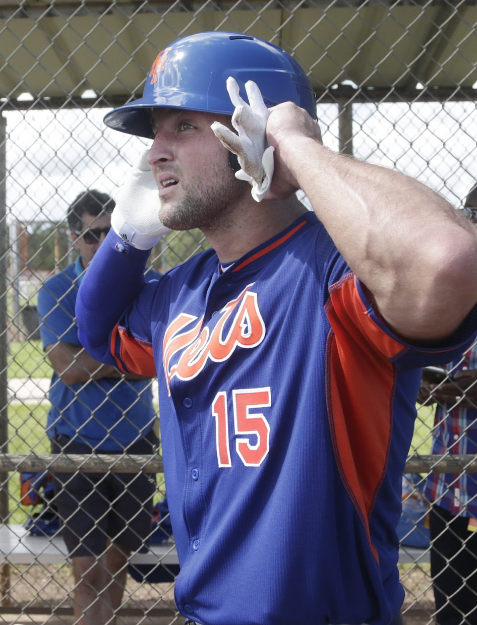 Tim Tebow puts on his batting helmet before practice at the New York Mets' complex, Monday, Sept. 19, 2016, in Port St. Lucie, Fla. The 2007 Heisman Trophy winner and former NFL quarterback got to the complex early Monday, and started his first workout as part of their instructional league team. (AP Photo/Wilfredo Lee)