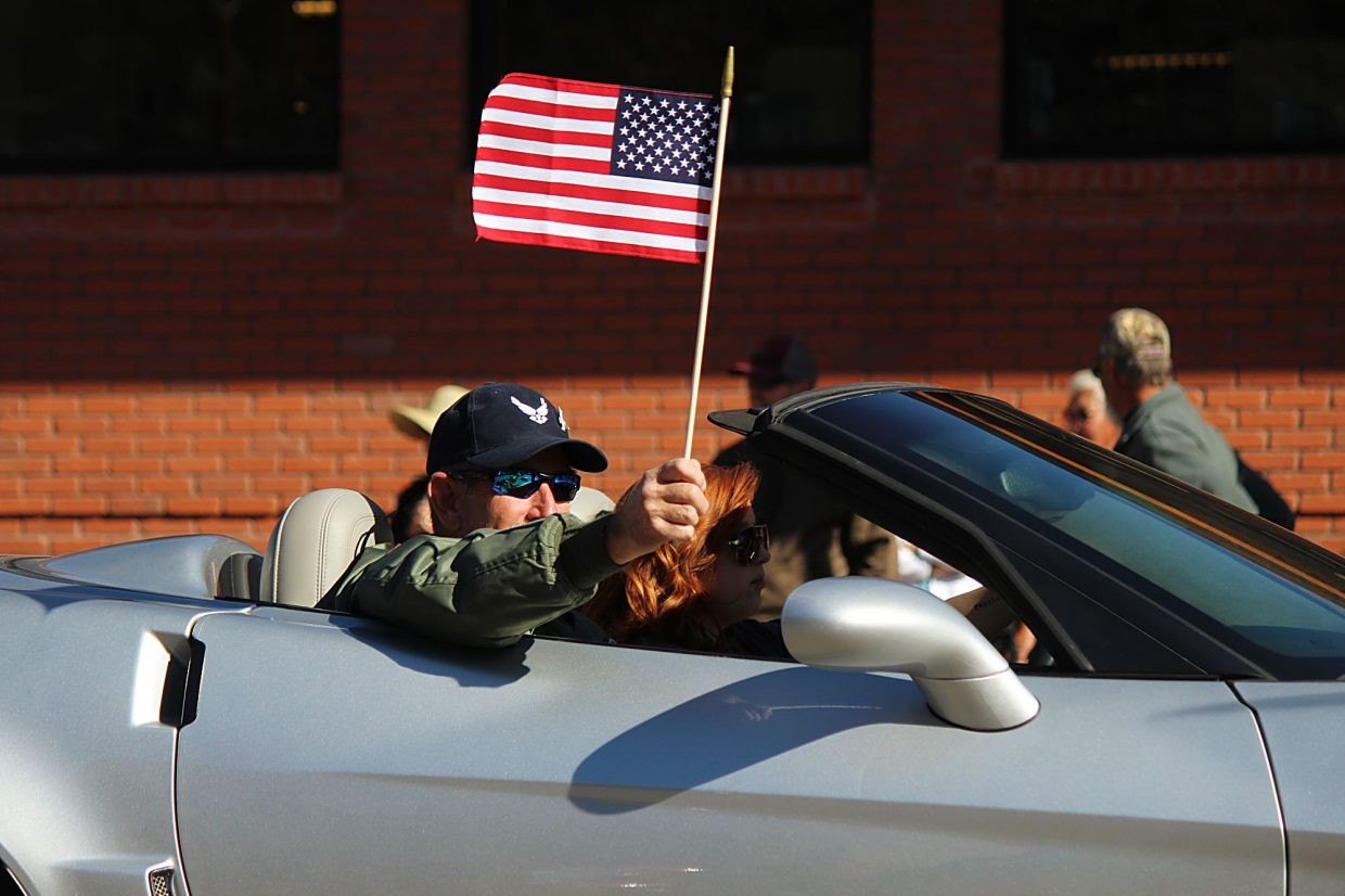 """Ham DuBois, father of Capt. Will """"Pyro"""" DuBois, waives an American flag during the Burning Mountain Festival parade in New Castle. A statue honoring Will, who was died in December 2014, was unveiled during a ceremony after the parade."""