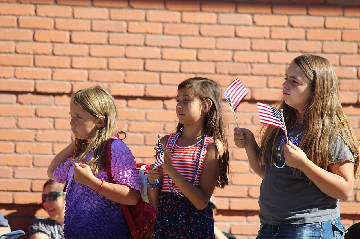 A group of young girls watch the annual Burning Mountain Festival parade in New Castle Saturday.