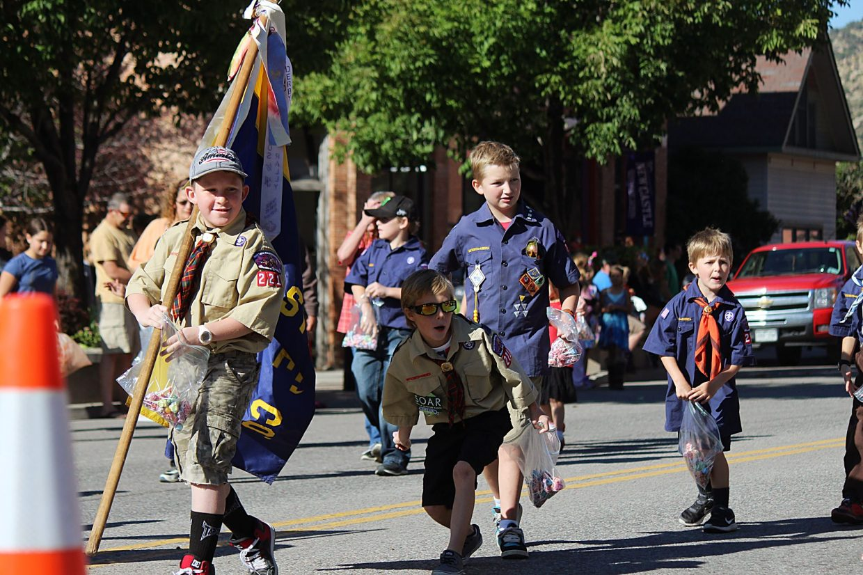 Members of Cub Scout Troop 221 toss candy to spectators.