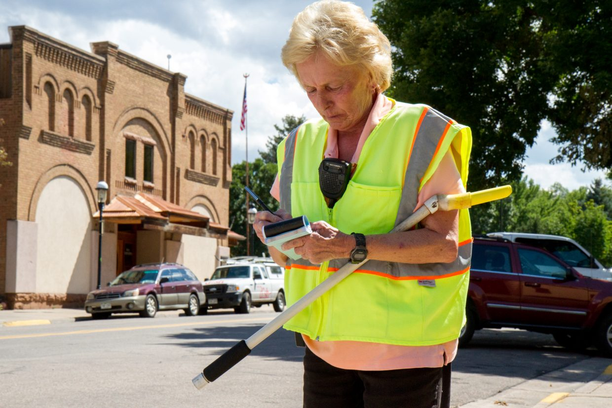 Parking Enforcement Officer Janie Daniels walks an estimated 10 miles a day marking cars and giving tickets for parking violations around downtown Glenwood Springs.