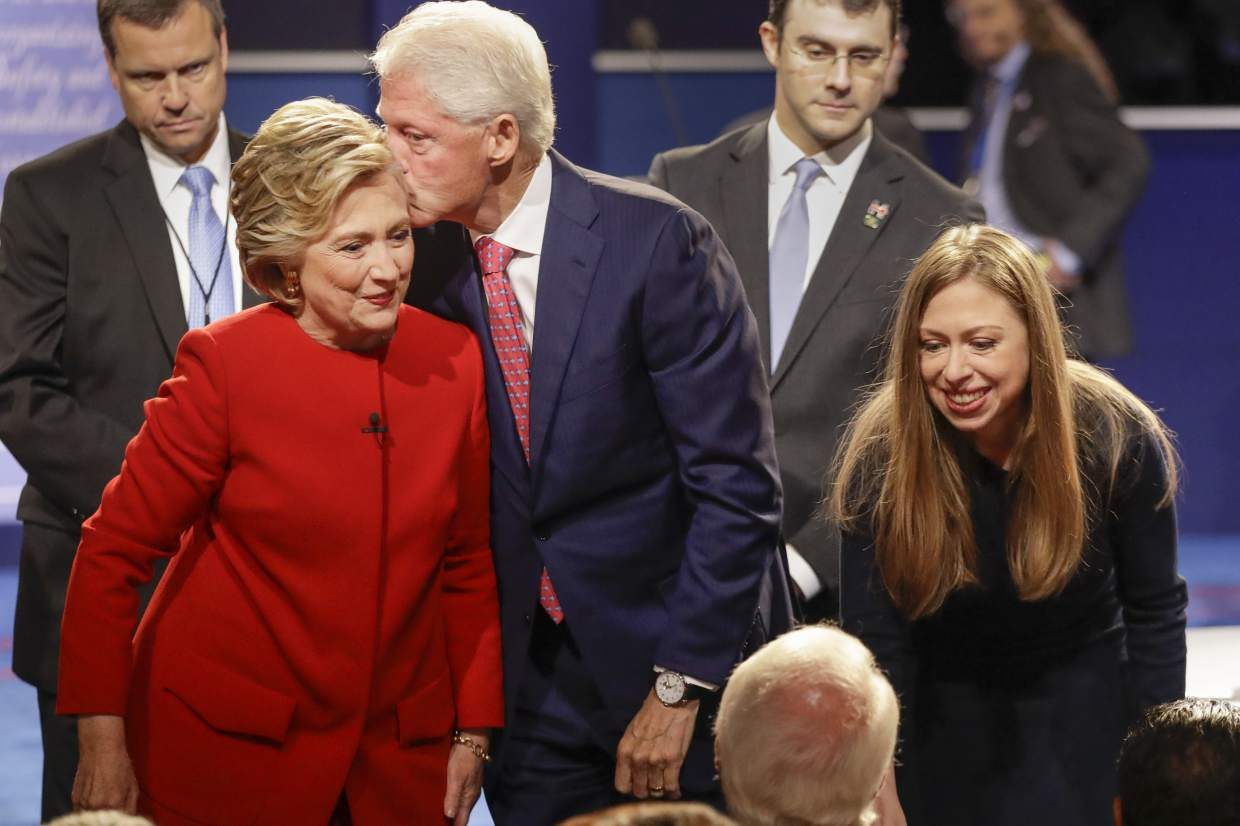 Former President Bill Clinton kisses Democratic presidential nominee Hillary Clinton as she and their daughter Chelsea Clinton greet supports during the presidential debate at Hofstra University in Hempstead, N.Y., Monday, Sept. 26, 2016. (AP Photo/David Goldman)