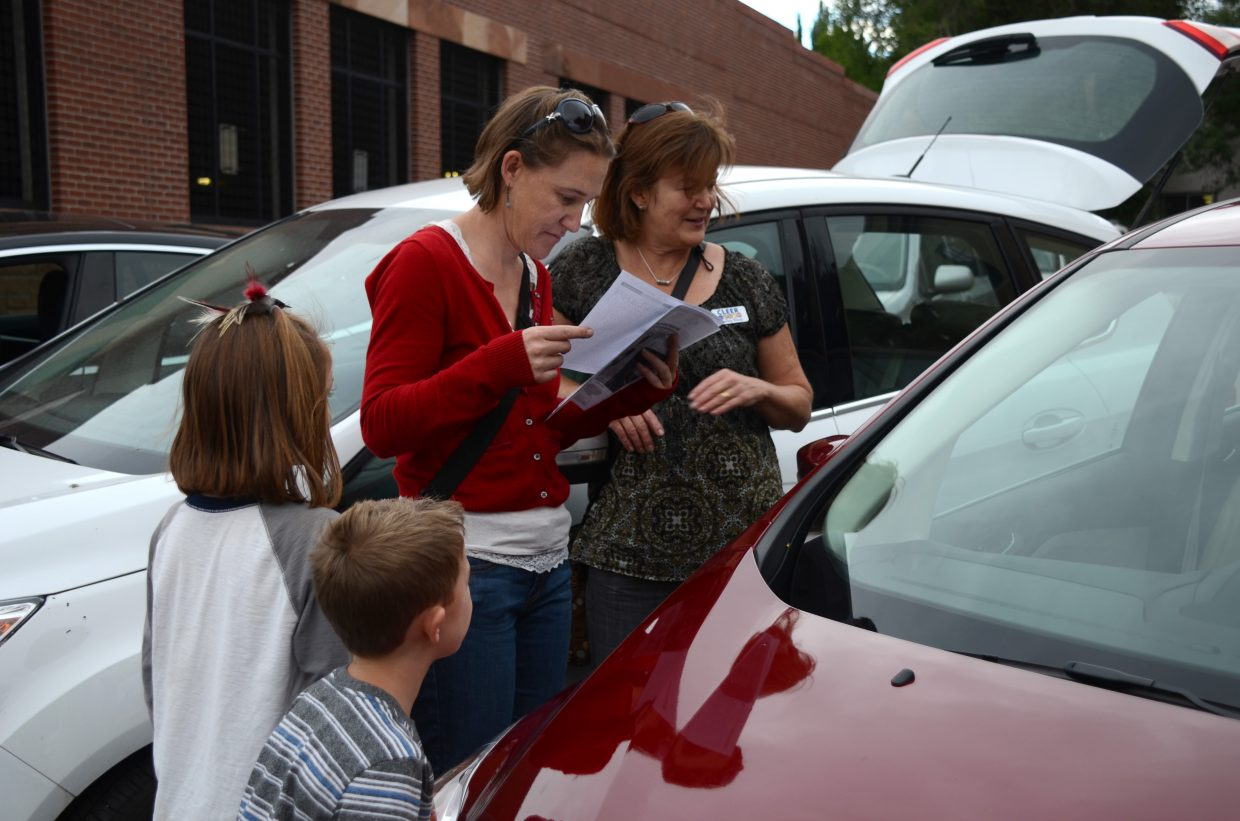 Shelley Kaup of CLEER shows the Conor Famly — Rachel, center, Madalynn and Walker John — her Ford C-Max as part of an electric car exhibit at the Glenwood Springs Downtown Market on Tuesday.