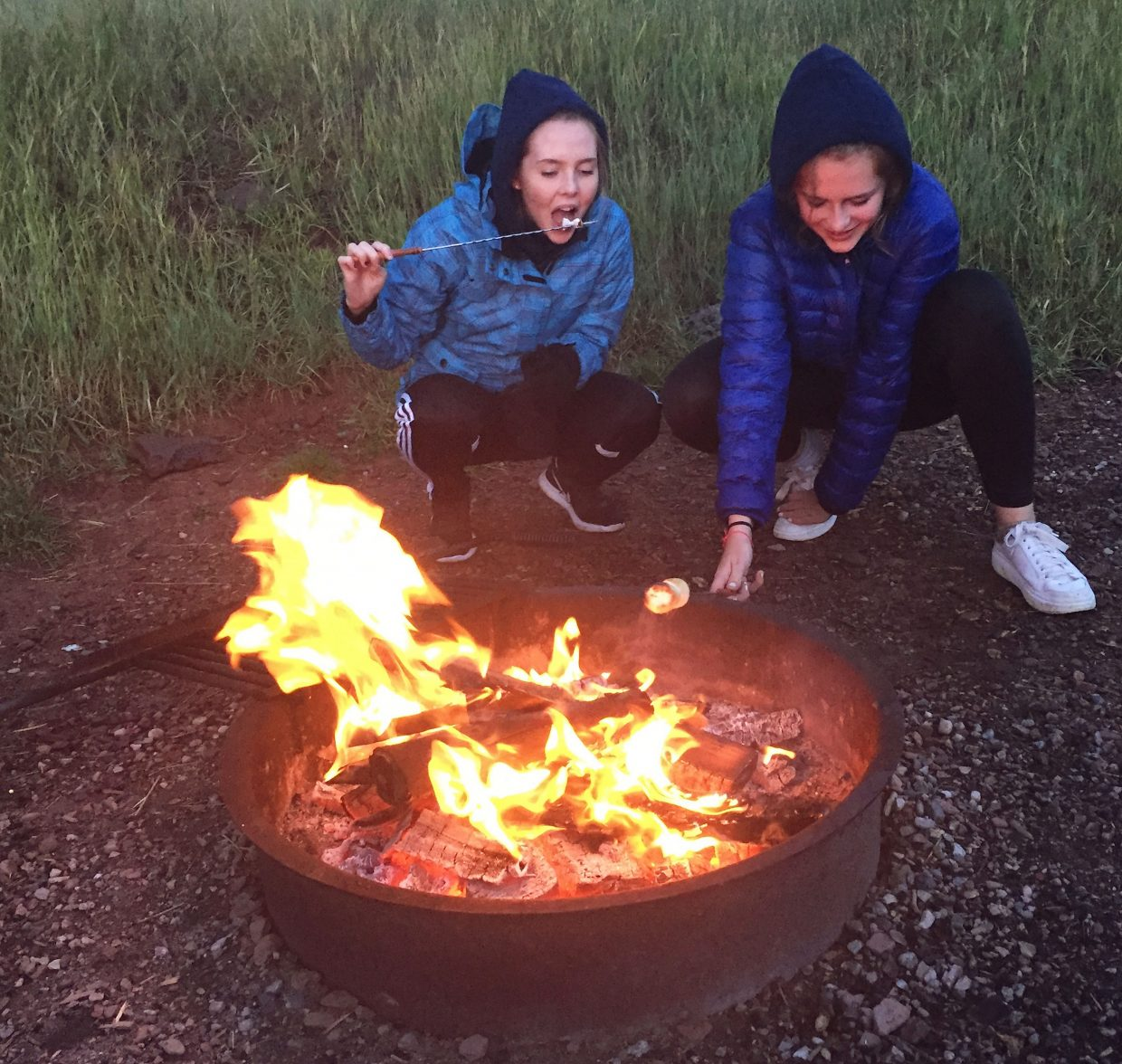 Camila, left, and Sophie, exchange students from Norway and Germany, respectively, enjoy their first taste of roasted marshmallows around the campfire over Labor Day weekend.