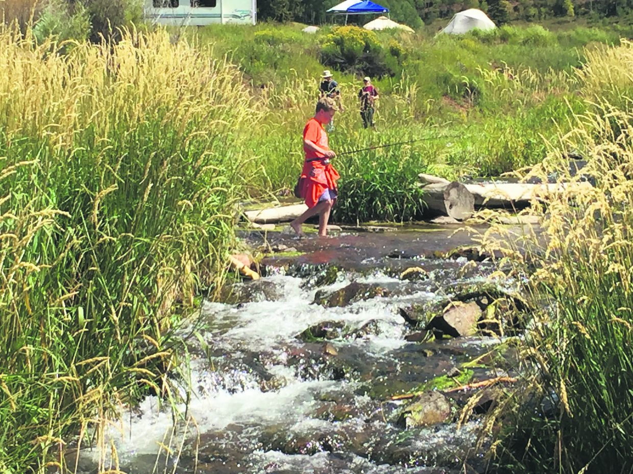 A young angler crosses Brush Creek just below Sylvan Lake.