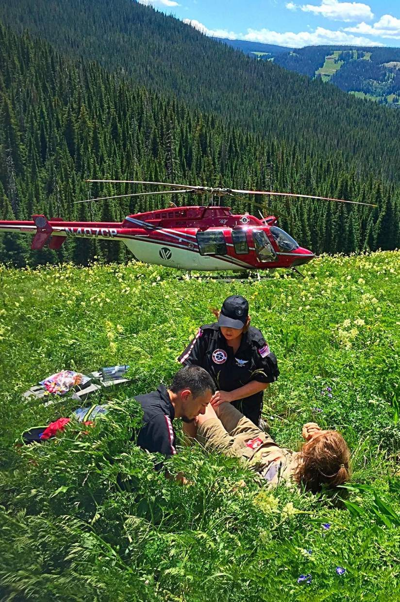 Nurse Stacy Lawson and paramedic Kraig Schlueter assess Mitch Stubbs' injuries on July 23 after he crashed paragliding on the Flat Tops and spent a night outdoors.