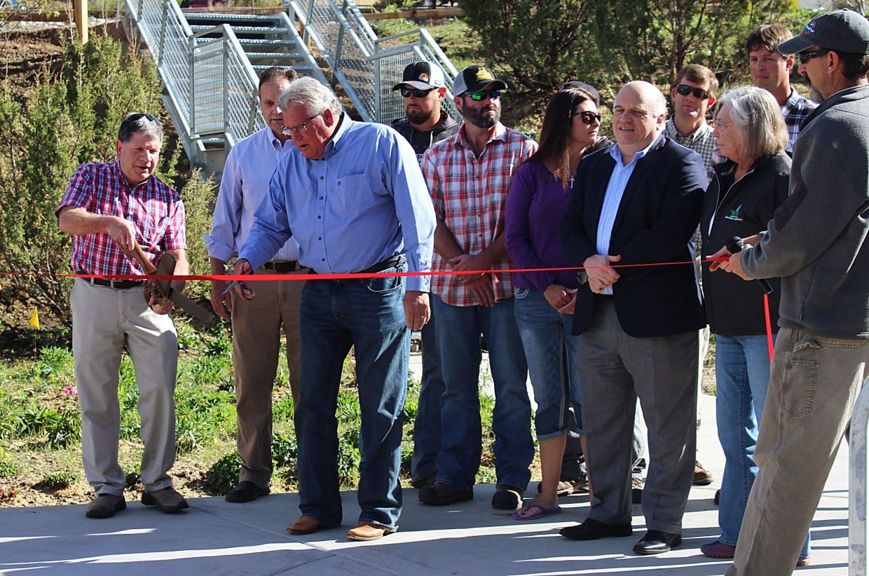 Surrounded by officials from Roaring Fork Transportation Authority and the Garfield County Federal Mineral Lease District, New Castle Mayor Art Riddile, far left, cuts the ribbon on the new RFTA park-and-ride Wednesday. The park-and-ride has been in the works since 2007 when the land, located at 774 Burning Mountain Drive, was purchased. The lot has 60 parking spaces, bike racks and electric vehicle charging stations.
