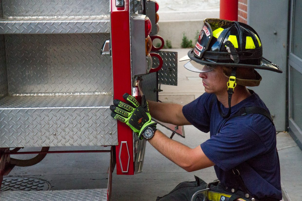 Kevin Carlson stabilizing the truck before raising and extending the ladder  during training at the downtown fire station.