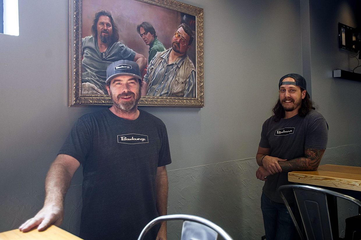 Craig Spivey, left, and Dillon McDermott of Bowlounge stand in the remodeled bar room under a painting on velvet of the main characters in 'The Big Lebowski.""