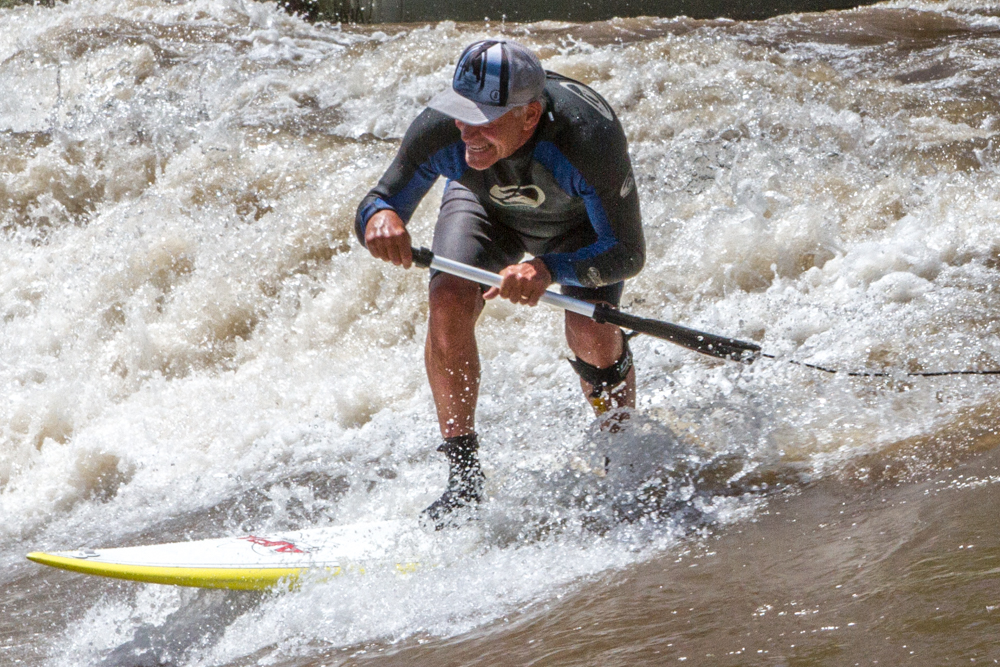 Tony Vongalis managed to catch a runaway paddle while surfing the wave. Large tree branches and various items are floating quickly down the river as the levels rise due to annual snowmelt in the high country.