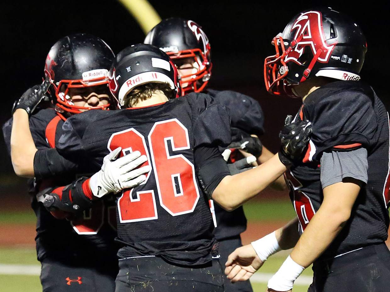 Aspen's Max Ufkes, No. 26, is congratulated by teammates after scoring a first-half touchdown against Coal Ridge on Friday.