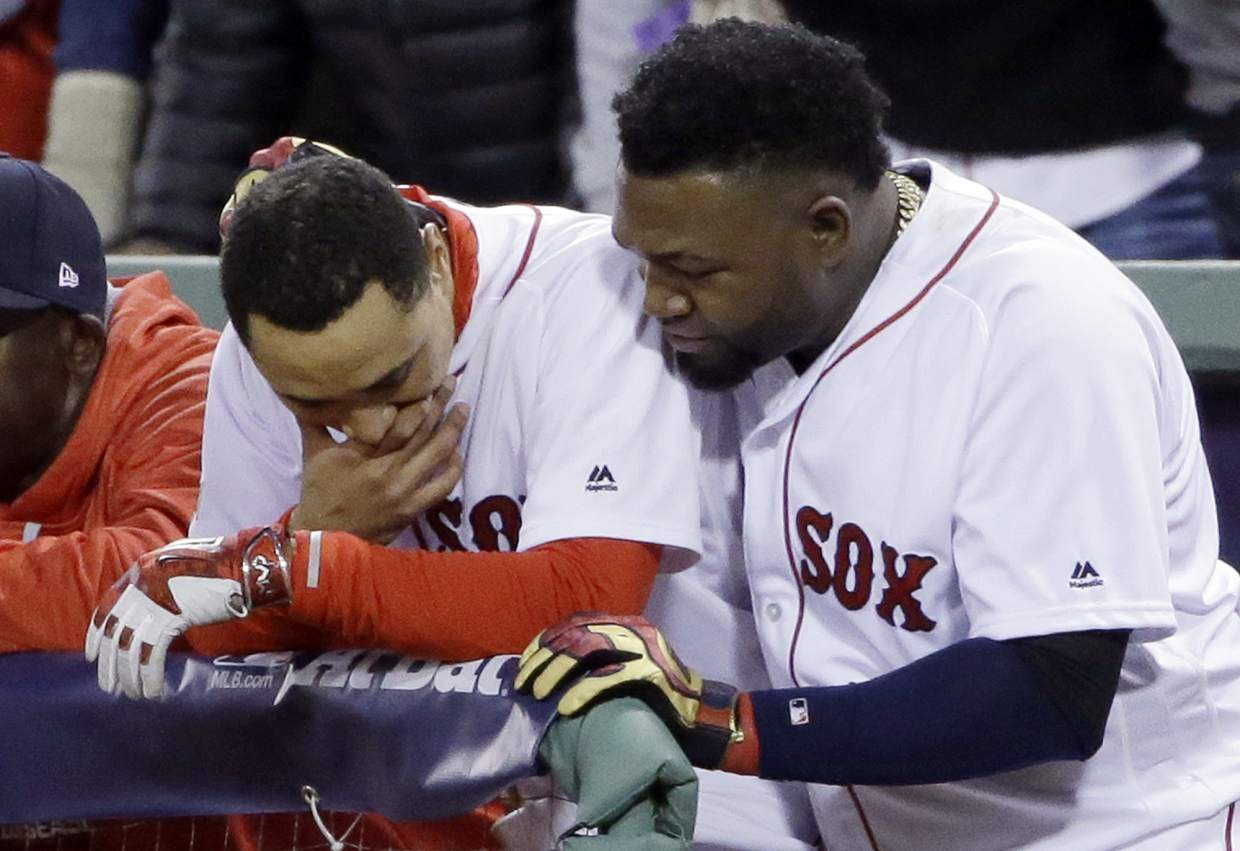 Boston Red Sox's David Ortiz, right, hugs Mookie Betts in the dugout during the eighth inning in Game 3 of baseball's American League Division Series against the Cleveland Indians, Monday, Oct. 10, 2016, in Boston. The Indians won 4-3 to sweep the Red Sox in the series. (AP Photo/Elise Amendola)