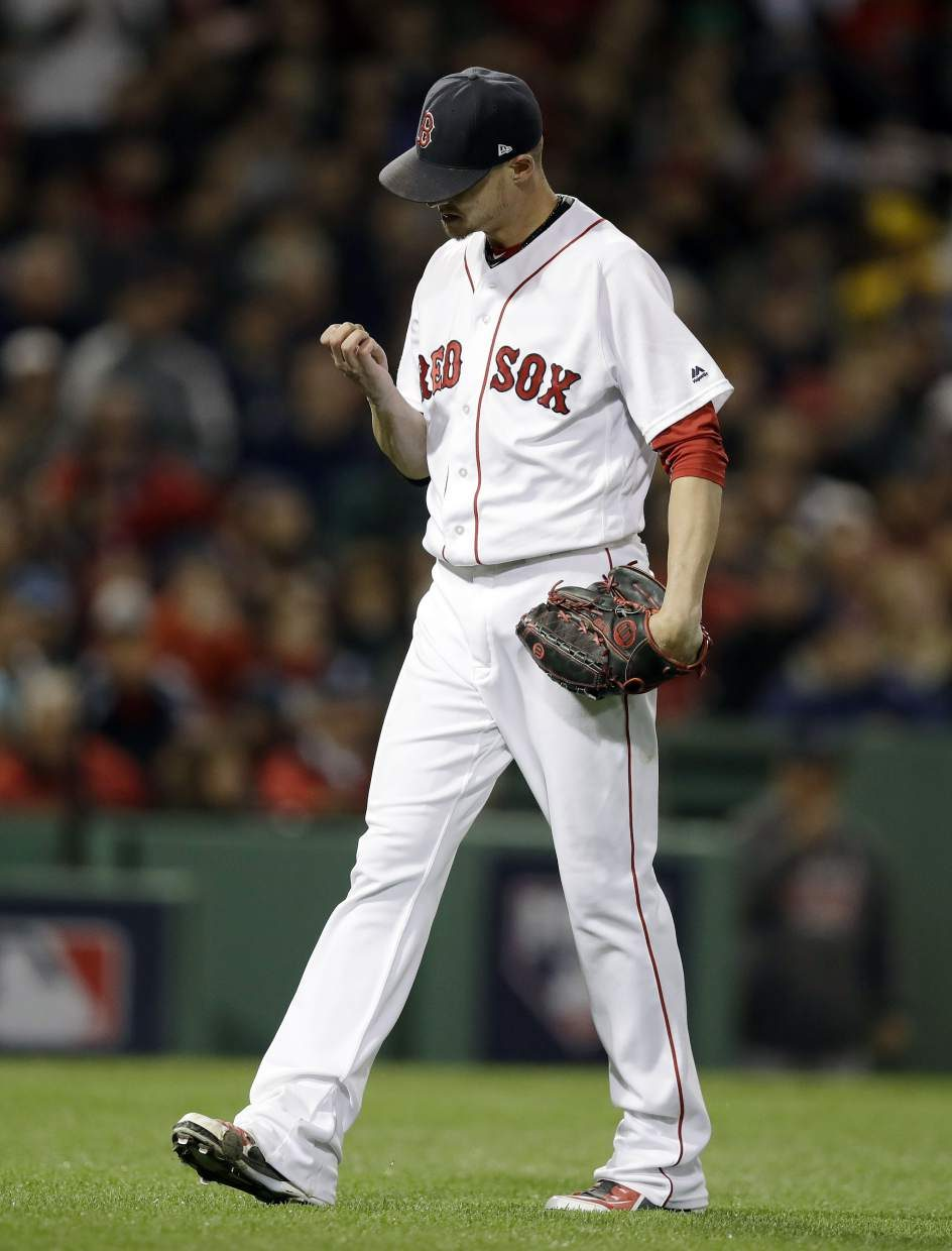 Boston Red Sox starting pitcher Clay Buchholz walks and looks at his his hand after giving up two runs to the Cleveland Indians during the fourth inning in Game 3 of baseball's American League Division Series, Monday, Oct. 10, 2016, in Boston. (AP Photo/Charles Krupa)