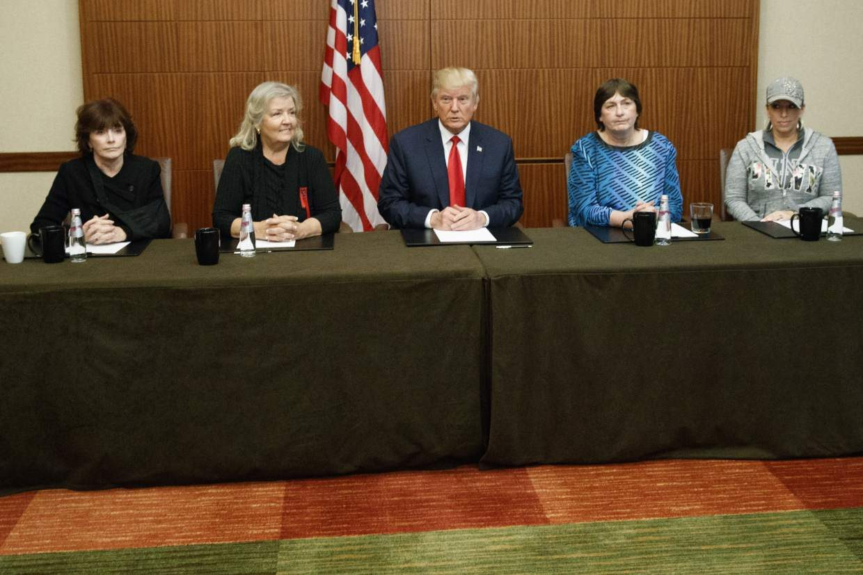 Republican presidential candidate Donald Trump, center, sits with, from right, Paula Jones, Kathy Shelton, Juanita Broaddrick, and Kathleen Willey, before the second presidential debate with democratic presidential candidate Hillary Clinton at Washington University, Sunday, Oct. 9, 2016, in St. Louis. (AP Photo/ Evan Vucci)