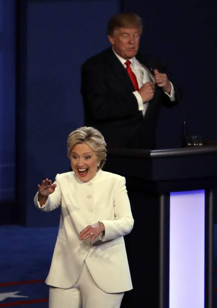 Democratic presidential nominee Hillary Clinton smiles as she walks past Republican presidential nominee Donald Trump at the end of the third presidential debate at UNLV in Las Vegas, Wednesday, Oct. 19, 2016. (AP Photo/Julio Cortez)