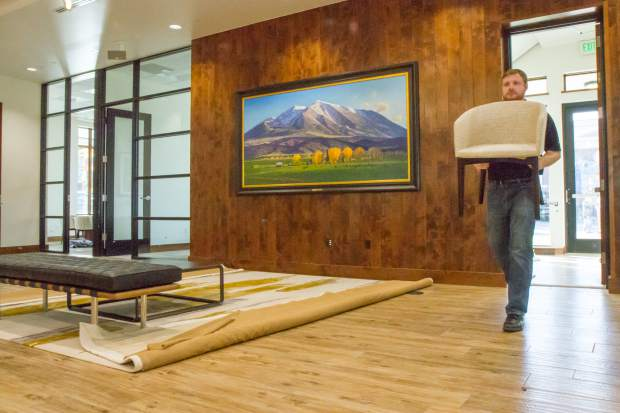 Jarred Houghton with Bank of Colorado helps to move in furniture during one of the last construction days of the new downtown building.