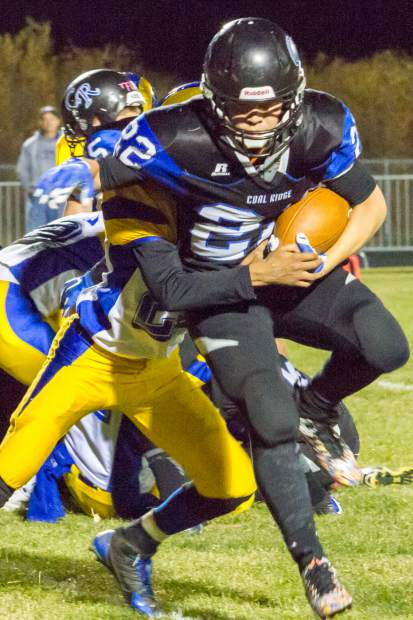 Coal Ridge TItan Eddy Baez (22) fighting to get the ball past the Roaring Fork Ram defense during Friday night's game at Coal Ridge HIgh School.