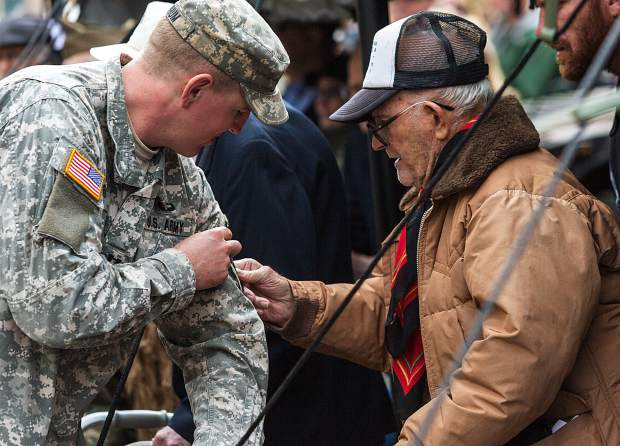 Clarence F. Dawson (Monk), veteran of the U.S. Army's 86th division company H, places a 10th Mountain patch on a 1-157th Infantry Army soldier during a re-patching ceremony Sunday at Camp Hale. Certain troops were chosen to receive their patches directly from WWII veterans like Dawson, as the first battalion, 157th Infantry became part of the third maneuver battalion of the 86th Infantry Battalion Combat Team under the 10th Mountain Division on Sunday.
