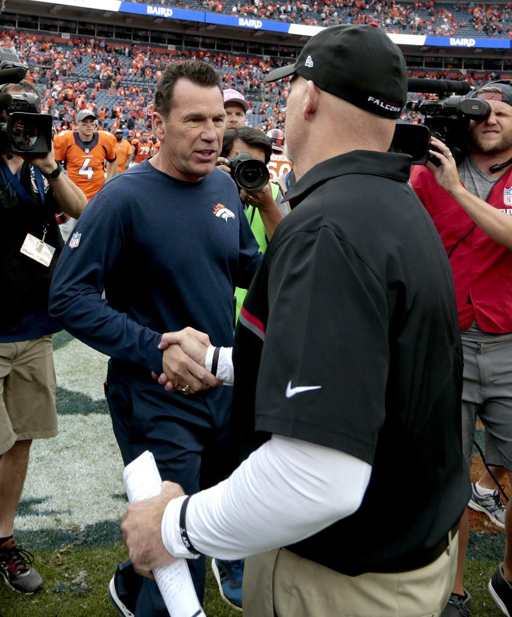 Denver Broncos head coach Gary Kubiak, left, greets Atlanta Falcons head coach Dan Quinn after an NFL football game, Sunday, Oct. 9, 2016, in Denver. The Falcons won 23-16. (AP Photo/Joe Mahoney)