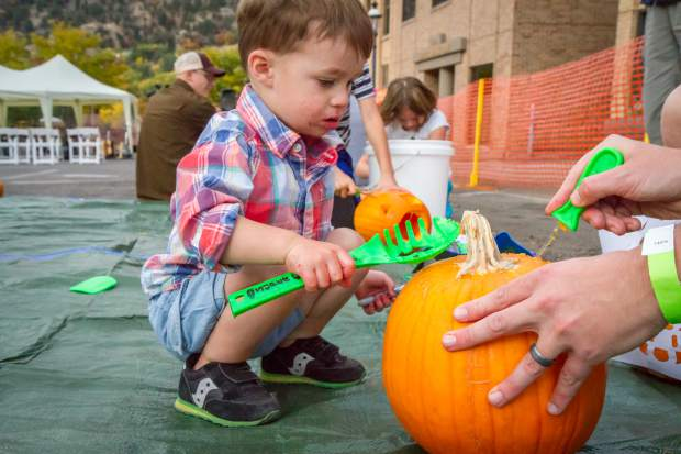 Landon Vaught (2) working on his pumpkin during the Glen-A-Palooza Lumber Jack Bash on Friday evening on Cooper Avenue.
