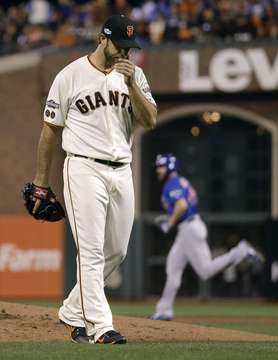 San Francisco Giants pitcher Madison Bumgarner, foreground, reacts after allowing a three-run home run to Chicago Cubs' Jake Arrieta, rear, during the second inning of Game 3 of baseball's National League Division Series in San Francisco, Monday, Oct. 10, 2016. (AP Photo/Ben Margot)