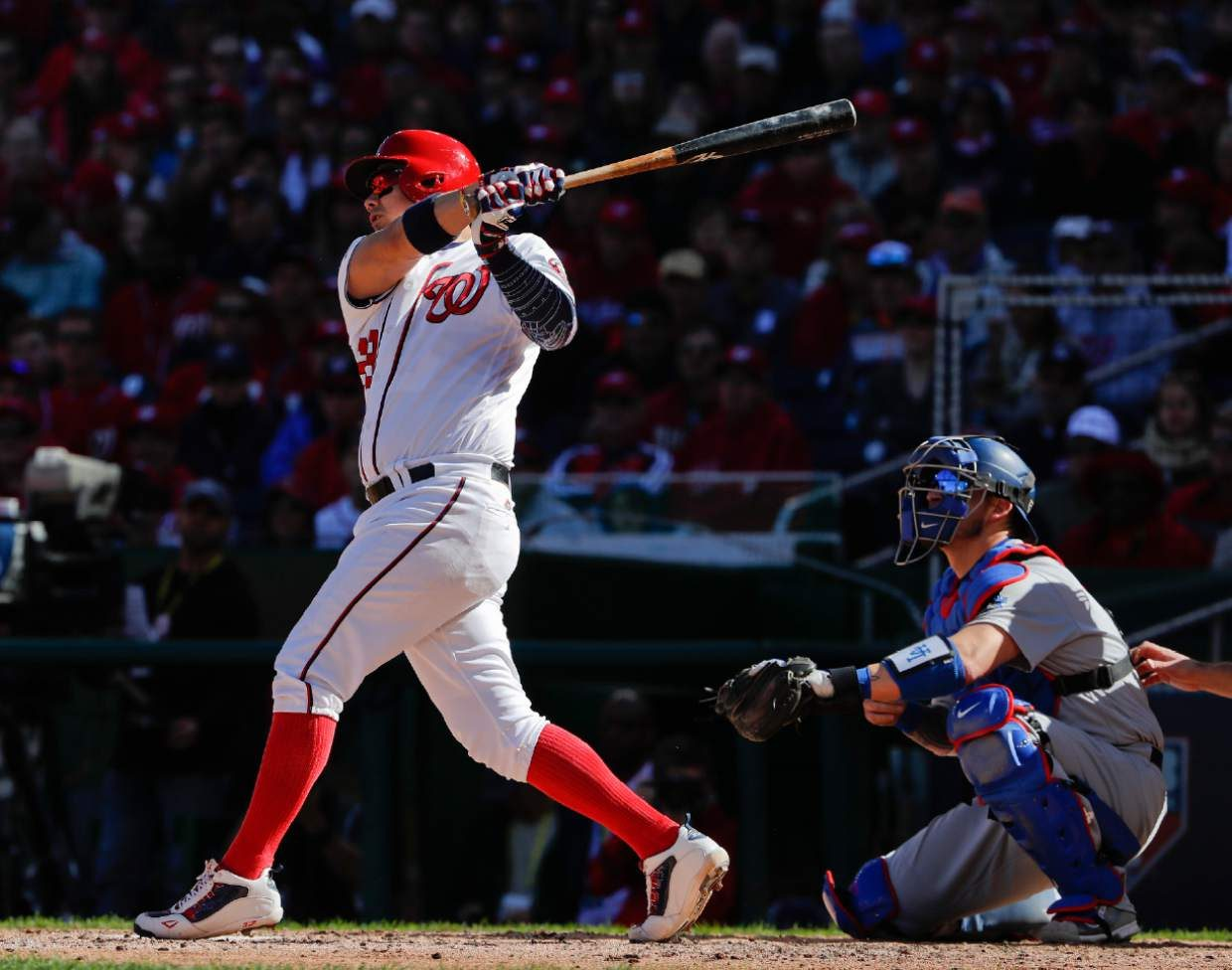 Washington Nationals' Jose Lobaton, left, connects for a three-run home run off Los Angeles Dodgers starting pitcher Rich Hill during the fourth inning in Game 2 of baseball's National League Division Series at Nationals Park, Sunday, Oct. 9, 2016, in Washington. Dodgers catcher Yasmani Grandal, right, looks on. (AP Photo/Pablo Martinez Monsivais)