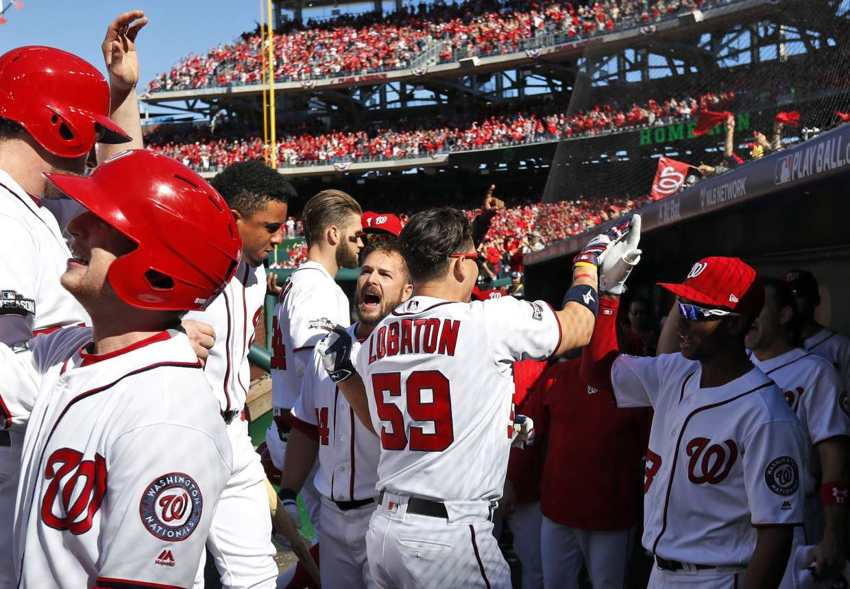 Washington Nationals' Jose Lobaton (59) and others, celebrate his three-run homer during the third inning of Game 2 of baseball's National League Division Series against the Los Angeles Dodgers at Nationals Park, Sunday, Oct. 9, 2016, in Washington. (AP Photo/Alex Brandon)