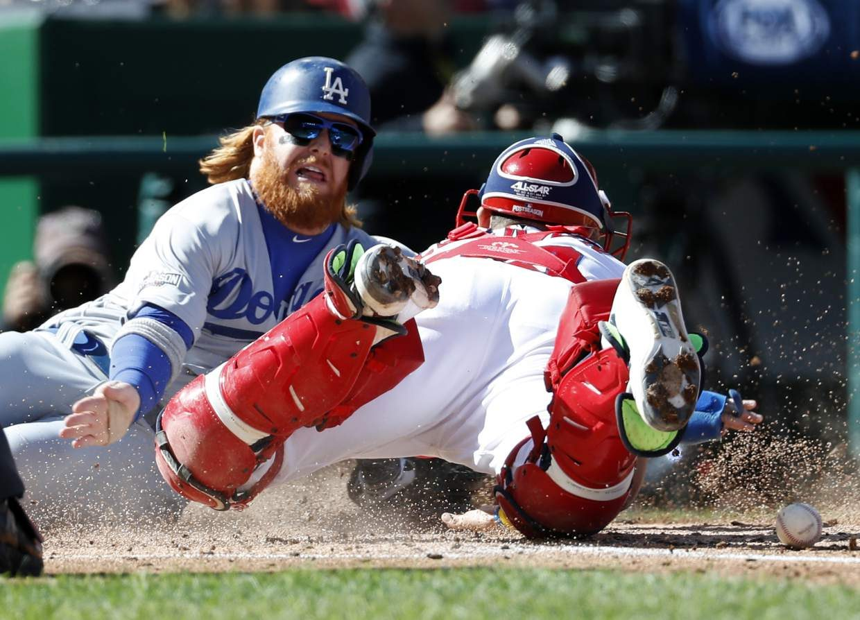 Los Angeles Dodgers' Justin Turner, left, is safe at home when Washington Nationals catcher Jose Lobaton cannot hang onto the ball in Game 2 of baseball's National League Division Series at Nationals Park, Sunday, Oct. 9, 2016, in Washington. (AP Photo/Alex Brandon)