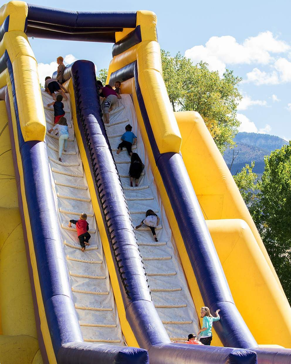 Children eagerly climb up a large inflatable slide Saturday.