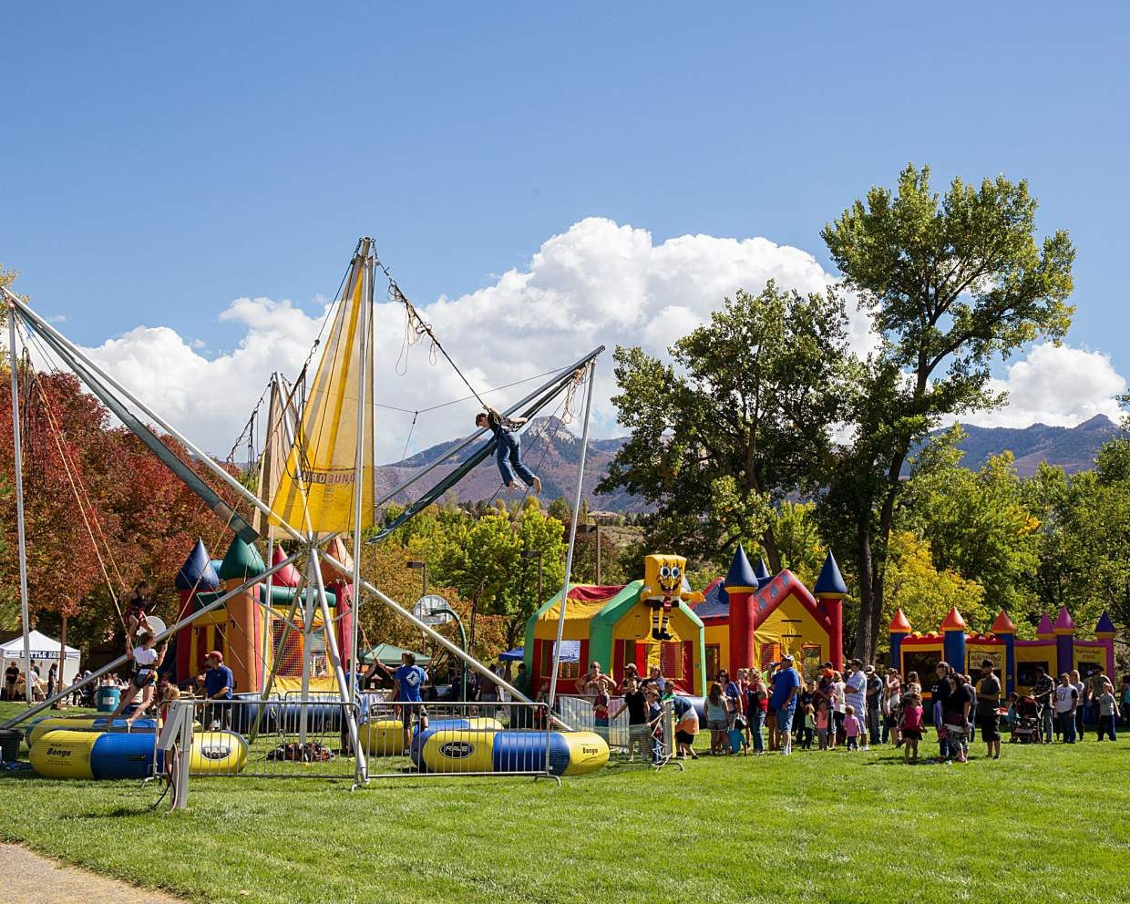 Children enjoy bounce houses and other rides in Cottonwood Park.