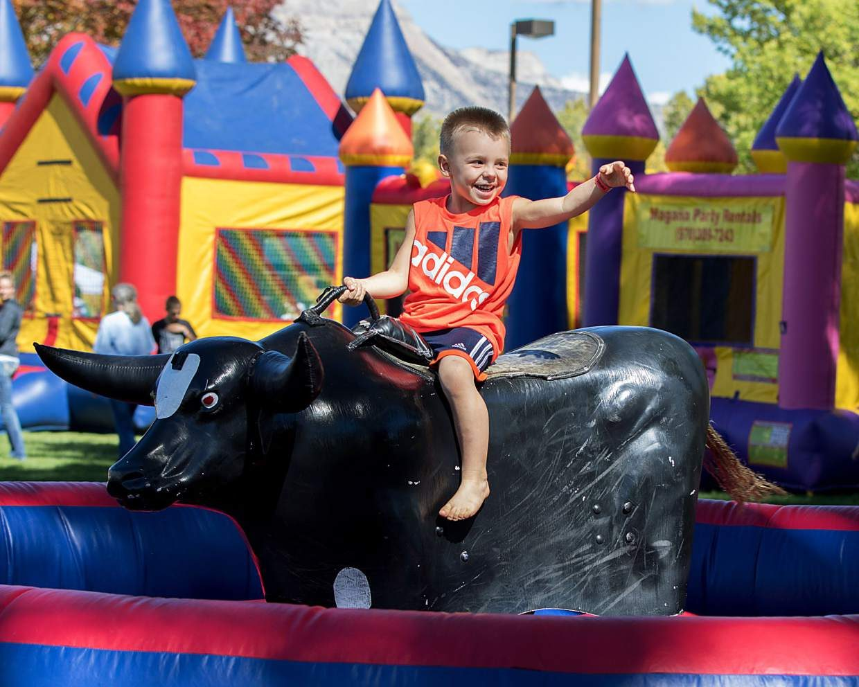 A young boy rides a mechanical bull.