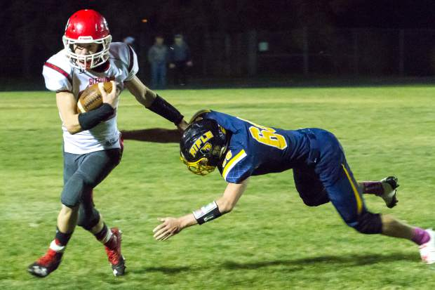 Demons QB Jake Townsley rushes past the Rifle Bears defense during Friday night's game at Rifle High School.